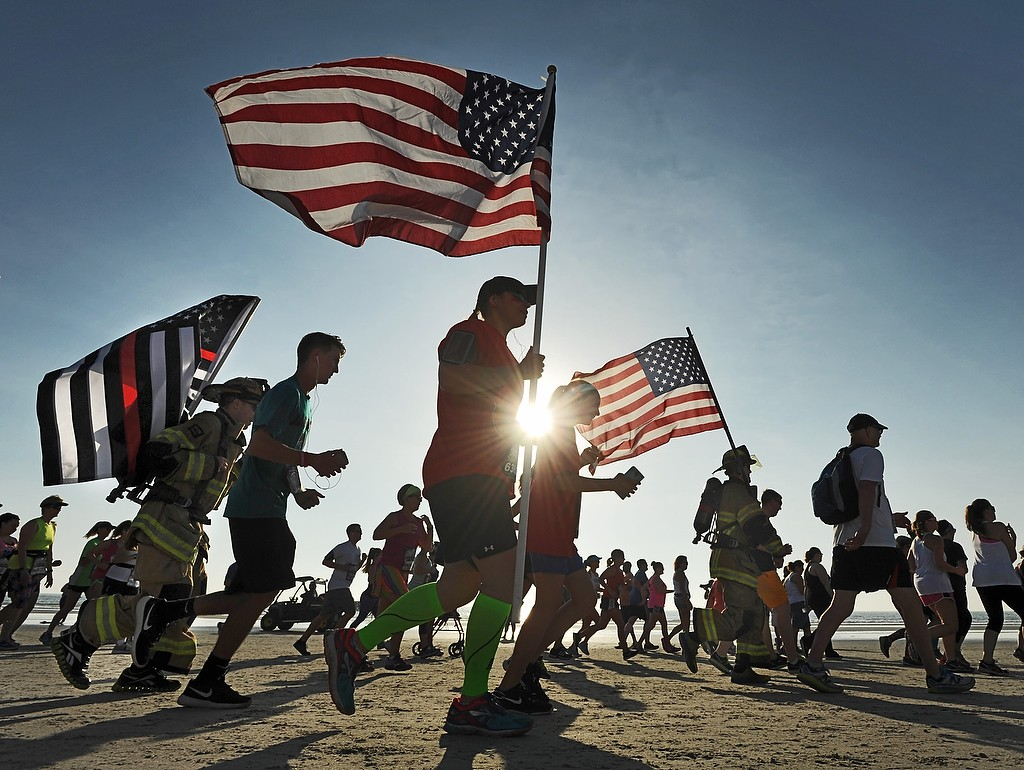 Will.Dickey@jacksonville.com--04/30/16--Runners carry U.S. flags at the start of the Never Quit 5k run Saturday morning, April 30, 2016 on Jacksonville Beach, Florida. The Never Quit events are inspired by long-time military veteran Gerard Petroni, who died in 2009. His son, Erik Petroni is the founder and director of Never Quit, which sponsors events around the world for the U.S. military, in addition to stateside running and other physical events that everyone can participate in. (The Florida Times-Union, Will Dickey)