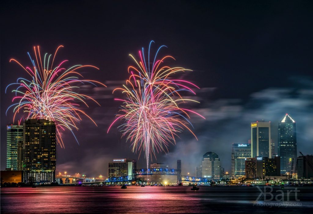 Colorful Fireworks explode over the downtown Jacksonville Florida skyline and the blue main street bridge